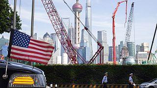 Sanghaj látképe, az előtérben egy amerikai követségi autó orrával