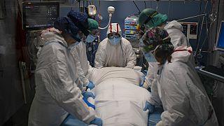 Varios sanitarios se preparan para rotar a un paciente de COVID en el Hospital del Mar, en Barcelona