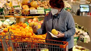 Una donna indossa una Ffp2 al supermercato, Vienna