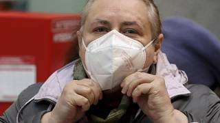 Uma mulher ajusta uma máscara protetora FFP2 ao fazer compras num supermercado em Viena, Áustria.