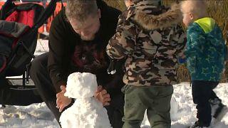 Vater baut Schneemann mit dem Sohn