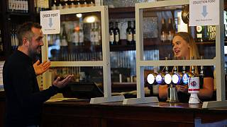 A man orders beer behind a safety screen at the Forester pub in London, Saturday, July 4, 2020