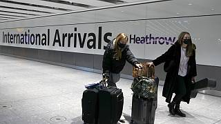 Travellers arrive at Heathrow Airport in London.