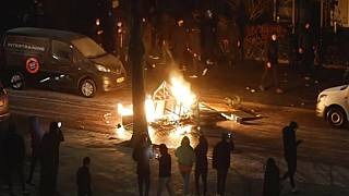 In this grab taken from video on Monday, Jan, 25, 2021, people use their phones to film items burning on a fire started by rioters, in Haarlem, Netherlands.
