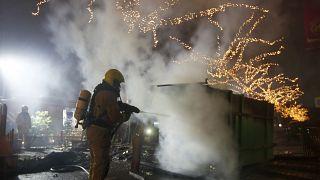Un bombero apaga un contenedor de basuras incendiado en Róterdam (25/01/21)