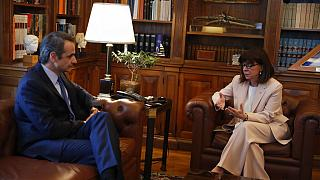 Greece's President Katerina Sakellaropoulou, right, talks to Prime Minister Kyriakos Mitsotakis