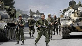 In this Thursday, Aug. 14, 2008 file photo, Russian soldiers block the road on the outskirts of Gori, northwest of the capital Tbilisi, Georgia.
