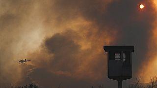 Egy tavalyi erdőtűz füstje Argentínában, a háttérben egy tűzoltó-repülőgéppel