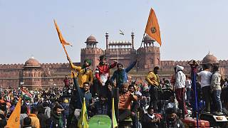 Sikhs wave the Nishan Sahib, a Sikh religious flag, as they arrive at the historic Red Fort monument in New Delhi, India, Tuesday, Jan. 26, 2021.
