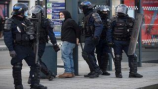 عناصر من الشرطة الفرنسية يعتقلون شخصاً في منطقة رين غربي البلاد