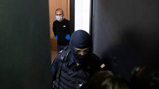 A police officer and an investigator stands behind the door of the apartment of jailed opposition leader Alexei Navalny in Moscow