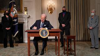 President Joe Biden signs a series of executive orders on climate change, in the State Dining Room of the White House, Wednesday, Jan. 27, 2021, in Washington.