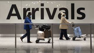 Arriving passengers walk past a sign in the arrivals area at Heathrow Airport in London, Tuesday, Jan. 26, 2021