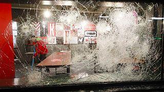 La vetrina di un fast-food a Rotterdam devastata dalle proteste