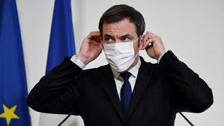 French Health Minister Olivier Veran adjusts his mask during a press conference on Tuesday Jan. 26, 2021 in Paris.