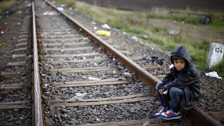 A young boy rests on the railway track near a temporary holding center for migrants near the border between Serbia and Hungary