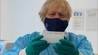 UK Prime Minister Boris Johnson with COVID-19 swab samples at Queen Elizabeth University Hospital in Glasgow.