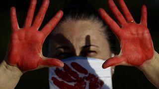 متظاهرة تظهر يديها المطلية باللون الأحمر والتي تمثل دماء أكثر من 200000 حالة وفاة بسبب كورونا في البرازيل