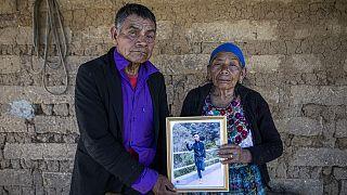 German y Maria Tomas posan para una fotografía sosteniendo un retrato enmarcado de su nieto Ivan Gudiel, en su casa en Comitancillo, Guatemala, el 27 de enero de 2021.