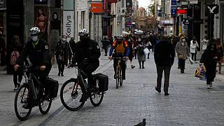Municipal policemen patrol with bicycles on Ermou Street