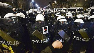 A Nők Sztrájkja matricája egy rendőr pajzsán Varsóban