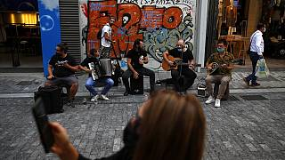 Musicians wearing face masks to prevent the spread of the coronavirus, perform as a woman records a video with her cellphone on Ermou Street,