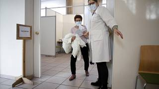 In this Jan. 18, 2021, file photo, a woman is guided to a vaccination booth prior to receiving the vaccination against COVID-19 at a vaccination center in Saint Denis