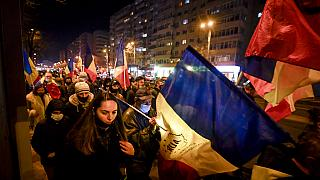 Protesters waving flags march after a deadly fire at a hospital treating COVID-19 patients in Bucharest, Romania, Saturday, Jan. 30, 2021.
