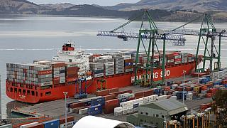 In this June 3, 2020, photo, containers are loaded onto a ship for export at Lyttelton Port near Christchurch, New Zealand.