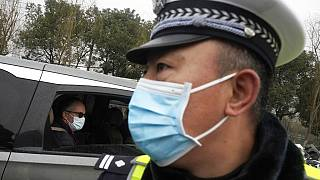 Peter Ben Embarek of the World Health Organization team passes by a Chinese police officer as he leaves in a convoy from the Baishazhou wholesale market