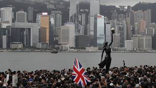 FILE - In this July 7, 2019, file photo, thousands of protesters carrying the British flag march near the harbor of Hong Kong.