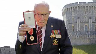Captain Sir Thomas Moore poses for the media after receiving his knighthood from Britain's Queen Elizabeth, during a ceremony at Windsor Castle in Windsor, England.