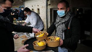 """French chef Stephane Turillon serves meals outside his restaurant """"La source bleue"""" in Cusance, eastern France, on February 1, 2021"""