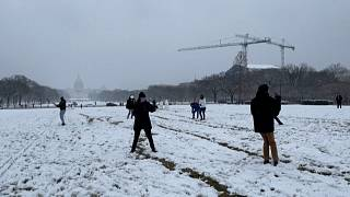 People partaking in a snowball fight, US Capitol in the background