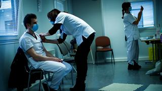 A health worker receives the coronavirus vaccine at a hospital in Liege, Belgium