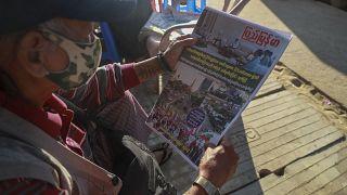 Un hombre lee en un periódico el anuncio de los militares en la capital birmana