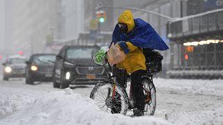 Un livreur à vélo tente de poursuivre son activité à New-York malgré la tempête de neige
