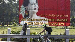 راكب دراجة هوائية، يمر عبر لافتة عليها صورة زعيمة ميانمار في يانغون، ميانمار.