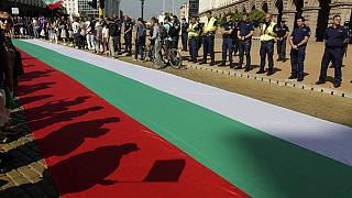 Protestors' shadows are cast on a giant Bulgarian flag amid demonstrations in Sofia demanding the government's resignation