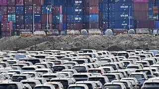 New cars are stored in front of containers at the 'logport' (logistic port) in Duisburg, Germany. Flle photo, Wednesday June 3, 2020.