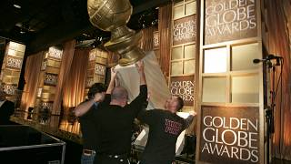 عمال يضعون جائزة غولدن غلوب على منصة المؤتمر الصحفي لإعلان الفائزين بجوائز غولدن غلوب السنوية الـ 65 في بيفرلي هيلز، كاليفورنيا.