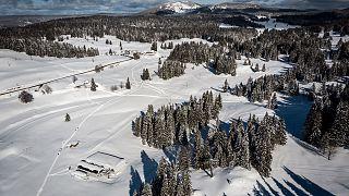 En bas, à gauche, une remontée de la station de Dôle en Suisse. Devant celle-ci, le parking de celle-ci en France, sous la neige le 26 janvier 2021
