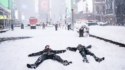 People make 'snow angels' during a snowstorm in Times Square, New York City
