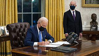 الرئيس الأمريكي جو بايدن يوقع على مراسيم متعلقة بالهجرة  فيما يقف إلى جانبه وزير الأمن الداخلي  أليخاندرو مايوركاس