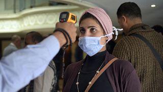 قياس درجة حرارة إمرأة مصرية في مدينة الإقصر وذلك في سياق الإجراءات التي اعتمدتها السلطات لمحاصرة جائحة كورونا.