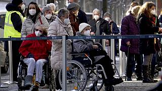 People queue in front of the vaccination center against the COVID -19 disease at the 'Arena Treptow' in Berlin, Germany, Monday, Feb. 1, 2021.