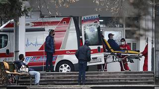 In this picture taken on Tuesday, Dec. 29, 2020, health workers wheel out a patient from an ambulance, at the entrance of the University Clinic complex in Skopje, North Macedo