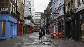A woman wears a face mask as she walks in a deserted Carnaby Street, in London, Wednesday, Feb. 3, 2021.