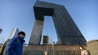 People walk past the CCTV Headquarters building, the home of Chinese state-run television network CCTV and its overseas arm CGTN, in Beijing on Feb. 4, 2021.