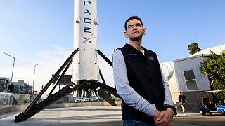 """الملياردير الأمريكي جاريد أيساكمان أمام صاروخ فالكون 9 في شركة """"سبيس إكس"""" للفضاء"""